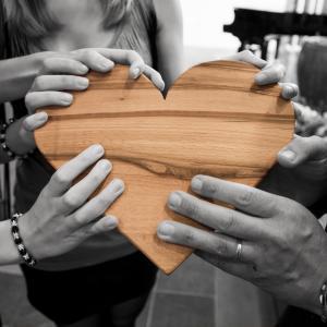 3 personen houden een houten hart vast